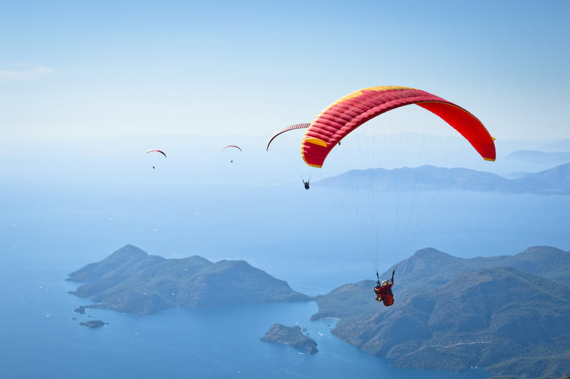 Red parachute above an island.