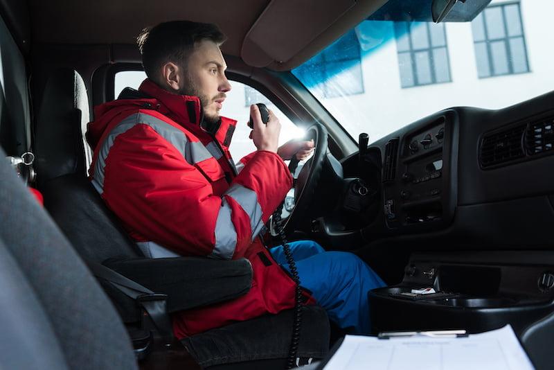 Male paramedic talking on portable radio.