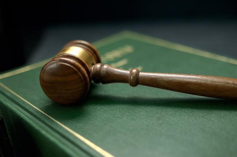 gavel on a law book, dark background.