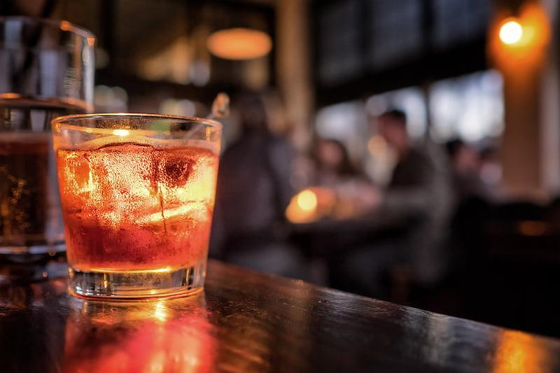 Alcoholic drink sitting on wooden bar, hazy background.