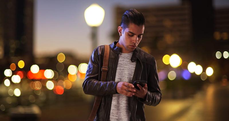 Millennial Hispanic man standing on city bridge at night looking at smartphone