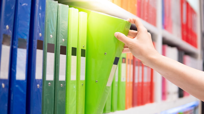 Male hand choosing new green ring binder file folder for new pain journal.