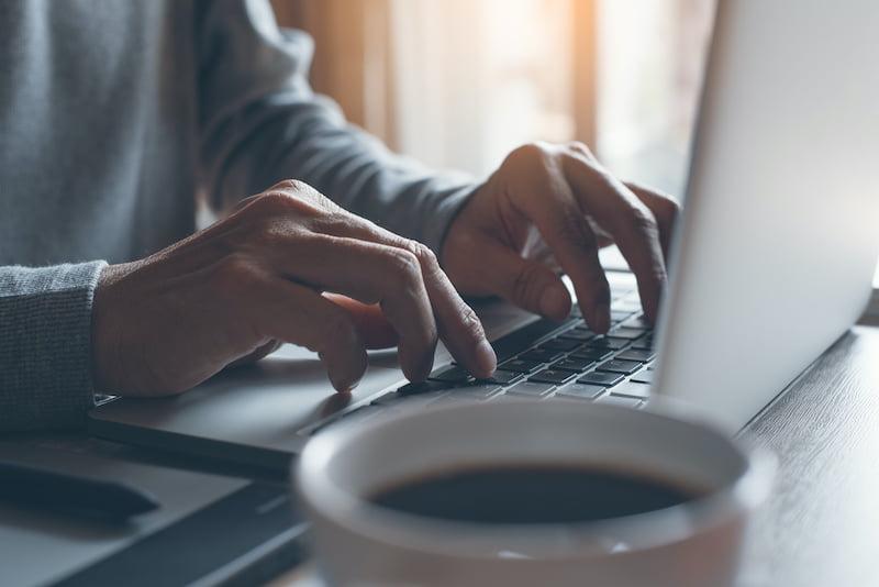 Business man or freelancer hand typing on laptop computer keyboard
